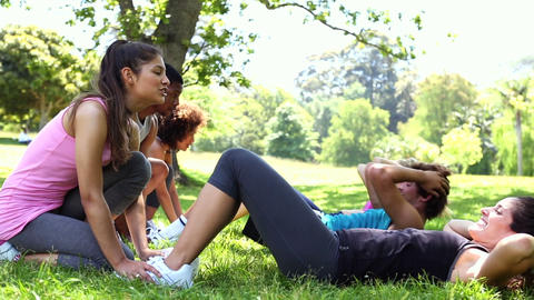 Fitness class doing sit ups in the park Footage