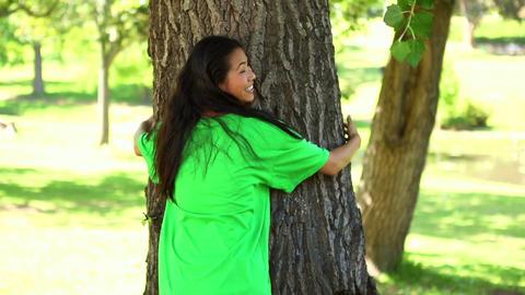 Happy environmental activist hugging a tree Footage