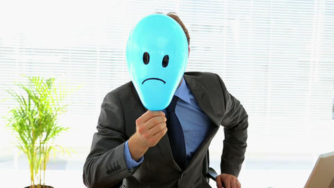 Grumpy businessman holding sad face balloon over face Footage