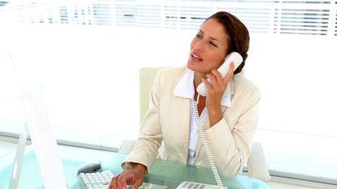 Businesswoman working at her desk and answering the phone Footage