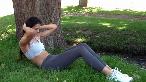 Fit brunette doing sit ups on the grass Footage