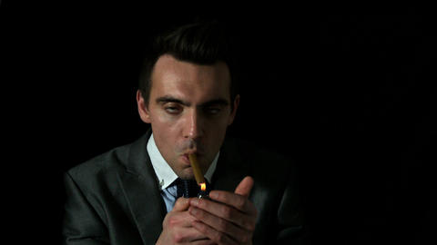 Businessman Lighting His Cigar On Black Background stock footage