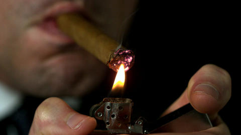 Businessman lighting his cigar on black background Footage