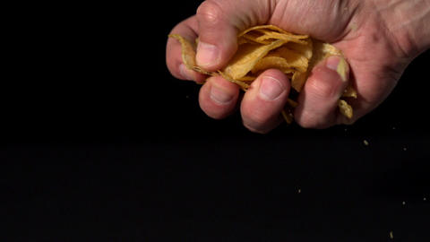 Hands crushing potato chips on black background Footage
