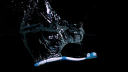Blue toothbrush falling in water on black backgrou Footage