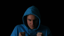 Sporty young man boxing on black background Live Action