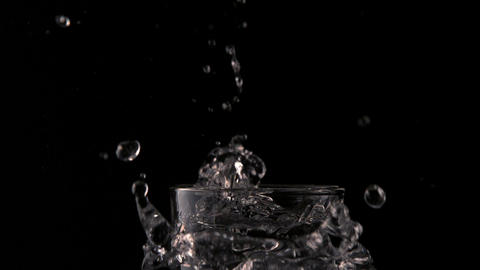 Ice cube falling into glass of water on black background Footage