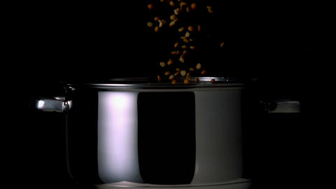 Popcorn kernels falling into pot on black backgrou Footage