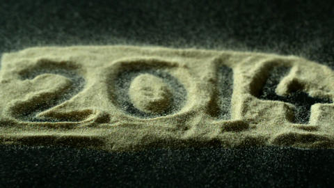 2014 spelled out in sand blowing away Footage