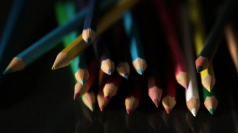 Colour pencils falling on black surface Footage