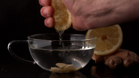 Hand squeezing lemon into cup of hot water and ginger Footage