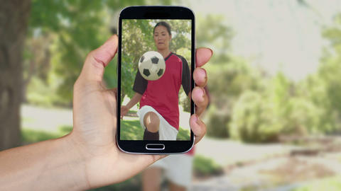 Hand showing girls playing football clips on smart Animation