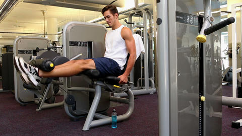 Fit man exercising his legs on weight machine Footage