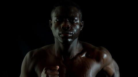Shirtless man jogging against black background Footage