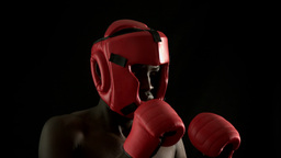 Tough boxer punching with red gloves Live Action