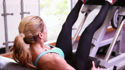 Super fit woman using the leg weights machine Footage