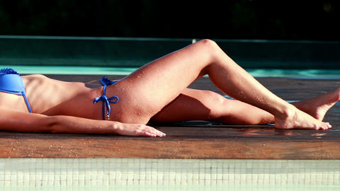 Sexy blonde in blue bikini relaxing lying poolside Footage