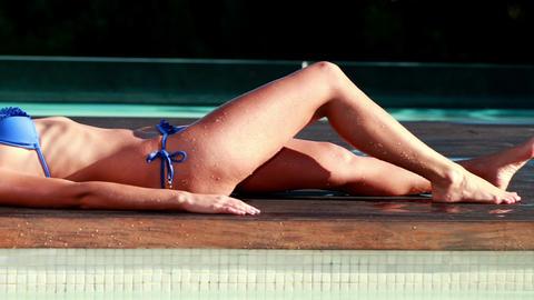 Sexy blonde in blue bikini relaxing lying poolside Footage