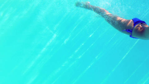 Sexy blonde in blue bikini diving into the swimmin Footage