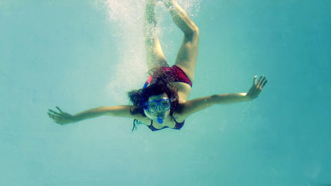 Fit brunette diving into swimming pool wearing sno Footage