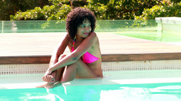 Gorgeous woman in pink bikini relaxing in swimming pool Live Action