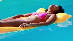Gorgeous woman in swimming pool lying on lilo Live Action