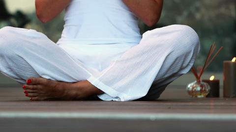 Woman in white sitting in lotus pose Footage