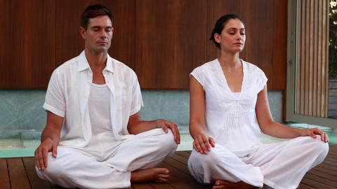 Calm couple in white sitting in lotus pose Footage
