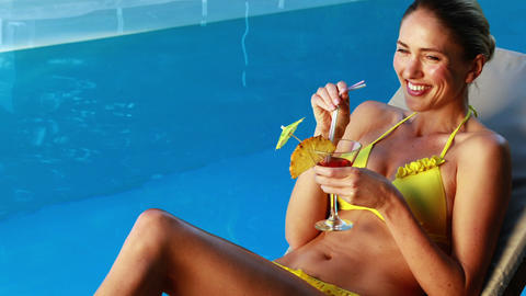 Gorgeous blonde in bikini enjoying a cocktail poolside Live Action