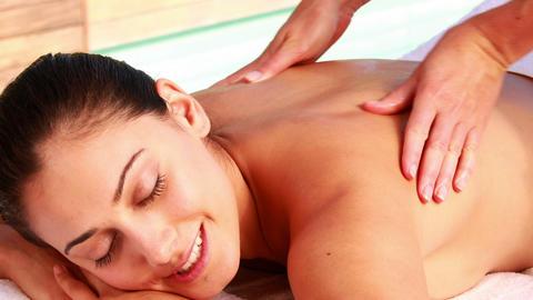 Happy brunette enjoying a massage poolside Footage