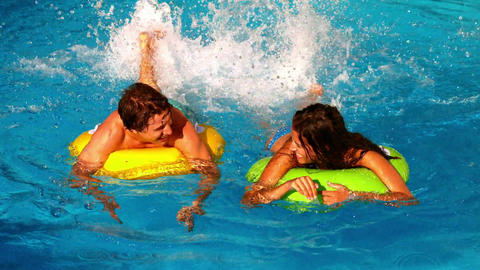 Young couple splashing and having fun in swimming  Footage