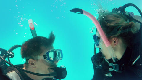 Couple in scuba gear looking at each other underwa Footage