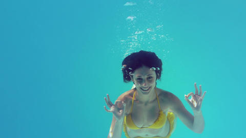 Gorgeous brunette in yellow bikini swimming underwater Footage