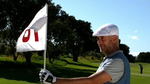 Smiling golfer holding eighteenth hole flag on golf course Live Action