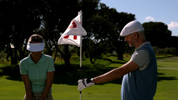 Smiling golfer holding eighteenth hole flag for his partner Live Action