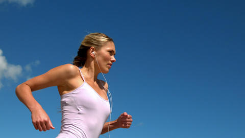 Fit blonde jogging and listening to music on sunny day Footage