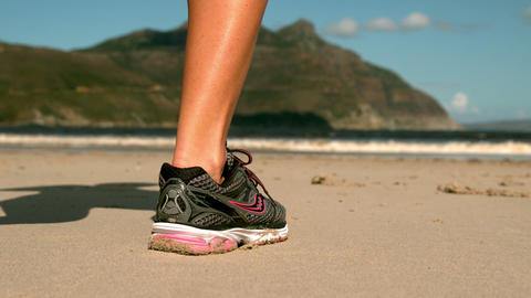 Woman jogging on the sand Footage