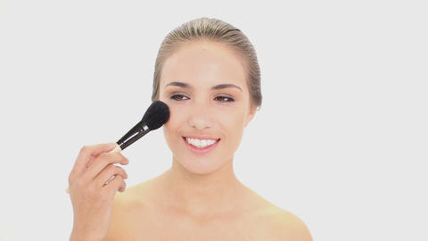 Beautiful model using a powder brush on her face Footage