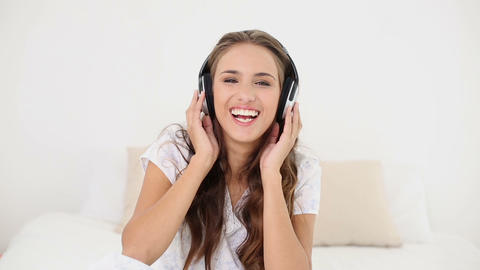 Young woman listening to music and dancing on her  Footage
