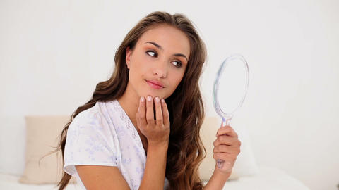 Young woman admiring herself in hand mirror Footage