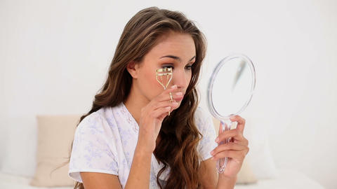 Young woman curling her eyelashes and looking in h Footage