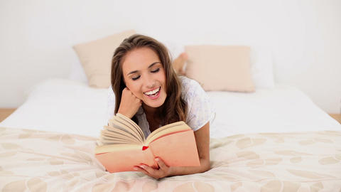 Young woman reading a book lying on her bed Footage