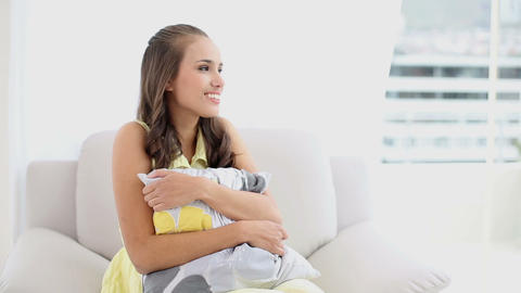 Young woman relaxing on her couch smiling at camer Footage