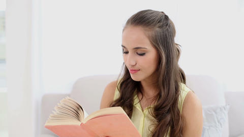 Young woman smiling and reading a book on the couc Footage