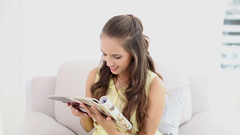 Young woman smiling and reading a magazine on the  Footage