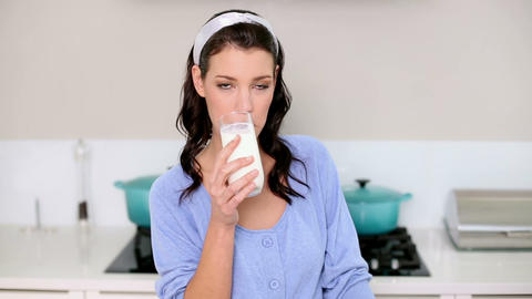 Beautiful brunette drinking a glass of milk Footage