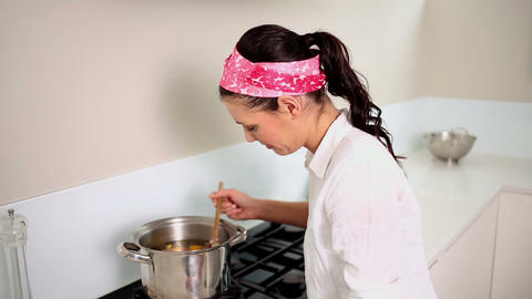 Beautiful brunette preparing a soup Footage