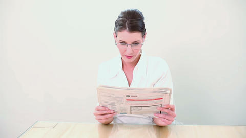 Beautiful brunette reading the newspaper Footage