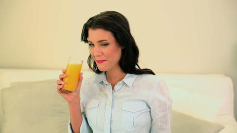 Beautiful brunette drinking a glass of orange juic Footage