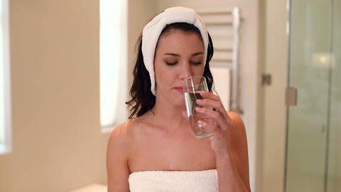 Beautiful brunette wearing a towel drinking a glas Footage